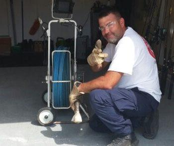 Video pipe inspection service technician kneeling next to equipment